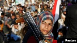 A girl carries a weapon as she attends a rally by followers of the Shi'ite Huthi movement in Yemen's capital, Sanaa, on October 26.