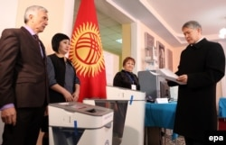 Kyrgyz President Almazbek Atambaev (right) arrives to cast his ballot at a polling station during the referendum on constitutional changes in Bishkek on December 11.