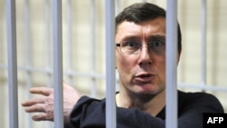 Former Ukrainian Interior Minister Yuriy Lutsenko gestures from a caged area during a court hearing in February.