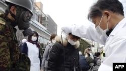 Дарыгер аскердин көзөмөлү астында аялдын радиация деңгээлин текшерүүдө. Фукусима перфекти, Нихонмацу шаары.