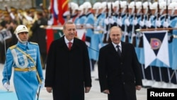 Russian President Vladimir Putin (right) and his Turkish counterpart, Recep Tayyip Erdogan, review an honor guard during a welcoming ceremony in Ankara on December 1.