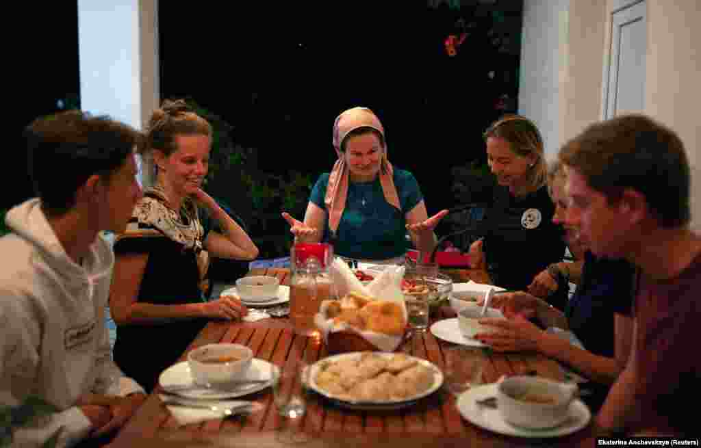 "Leila Achishvili (center), a guesthouse owner in Jokolo whose two sons were killed fighting in Syria, at dinner with tourists. Photographer Anchevskaya told RFE/RL: ""In Pankisi, they say if you are a guest of someone in the village, you are the guest of the whole village. These people have been through a lot and still face prejudice and conflicts, but they respect their guests, traditions, and nature they live in, and they want to share it with others."""