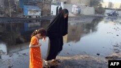 طفلة وأمها تتفاديان بقعة نفطية بعد إنفجار شاحنة حوضية تحمل وقود في بغداد