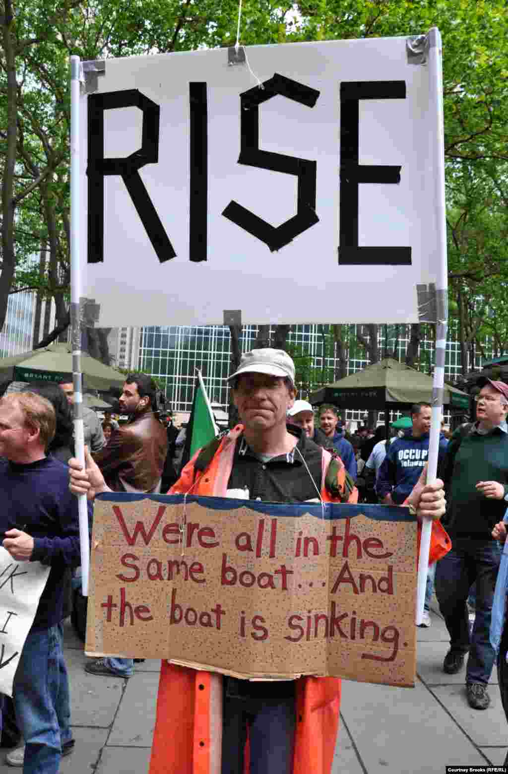 "An activist carries a sign warning that America is a sinking ship and calling on its citizens to ""rise."""