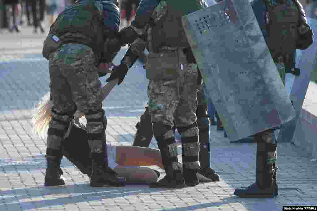 Police surround a woman in Minsk on August 11.