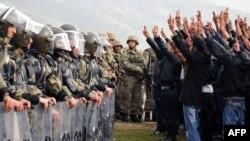 Курды выступают перед турецкими солдатами с требованием начать поиски жертв при столкновениях в селении Шырнак. 14 ноября 2012 года.