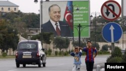 Azerbaijan -- Children wait for a bus in front of a billboard displaying a portrait of late President Heydar Aliyev, in Baku, 08Sep2012