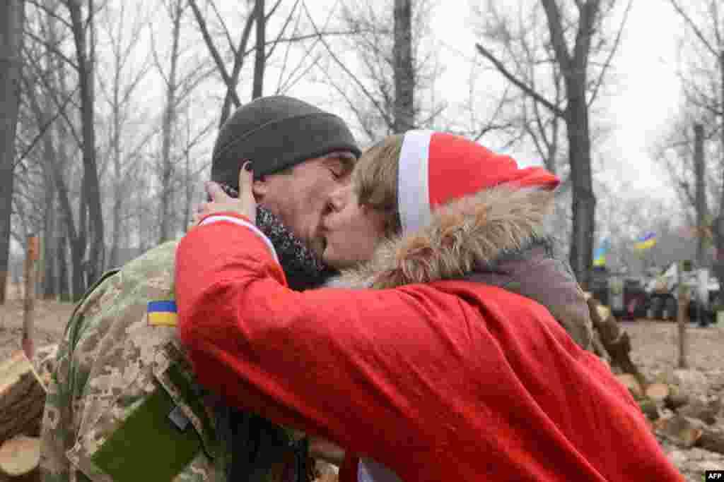 Волонтерка «Армії Допомоги» в костюмі Діда Мороза цілує військовослужбовця української армії під час новорічного вертепу на блокпосту біля міста Щастя, 28 грудня 2013 року