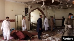 Members of a bomb-disposal unit survey the site after a blast at a mosque in Kuchlak, on the outskirts of Quetta, on August 16.