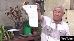Житель Алматы Зейш Коржинбаев сжигает акт о выселении из дома в Алматы. Скриншот с сайта YouTube. 8 апреля 2014 года.