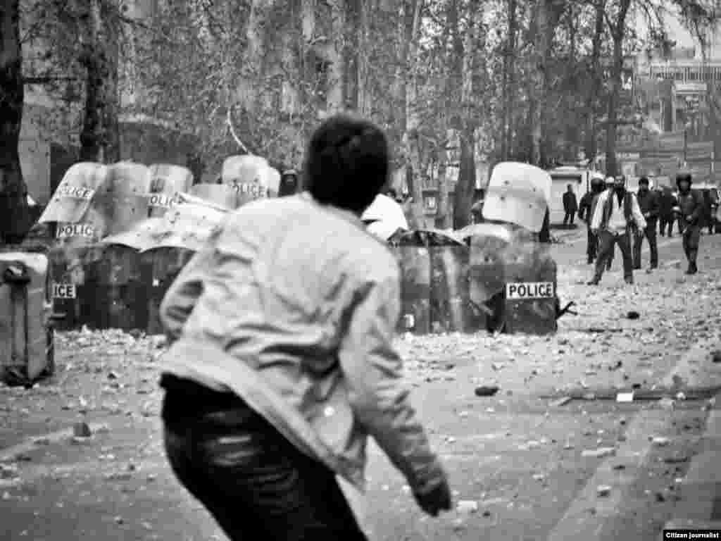 Iran -- Iranian opposition supporters throw stones towards riot policemen during clashes in Tehran on December 27, 2009.