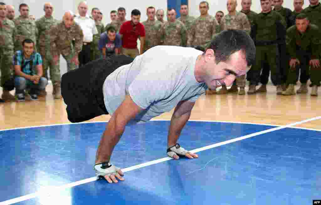 Corporal Temur Dadiani, 22, a double amputee military serviceman from Georgia sets the planche push-ups world record in one minute in Tbilisi on August 3. (AFP)