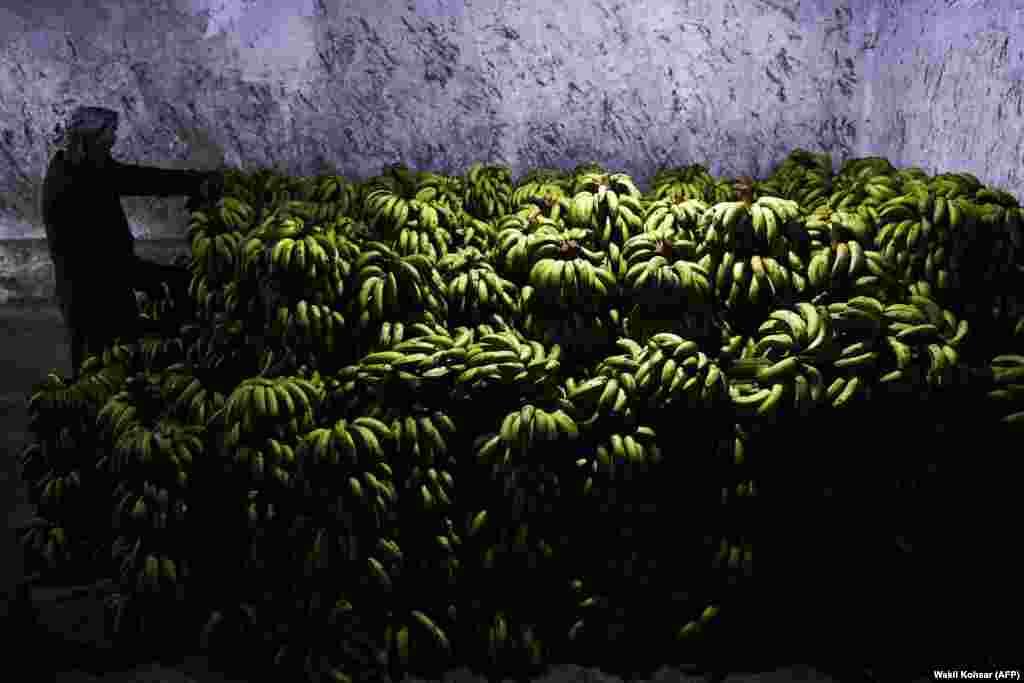 Працаўнік раскладвае бананы на кірмашы. Кабул, Аўганістан.