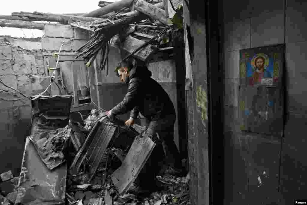 A local resident inspects debris inside his damaged home that locals say was caused by recent shelling in Makiivka, a town controlled by separatist forces in Ukraine's Donetsk region on March 24. (Reuters/Alexander Ermochenko)