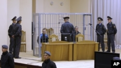 Surrounded by policemen, Dzmitser Kanavalaw (left) and Ulad Kavalyow are seen in a cage during their trial for the subway bomb in Minsk.
