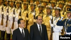 Iraqi Prime Minister Nuri al-Maliki (right), accompanied by Chinese Premier Wen Jiabao, reviews the military honor guard during a welcome ceremony at the Great Hall of the People in Beijing on July 18.