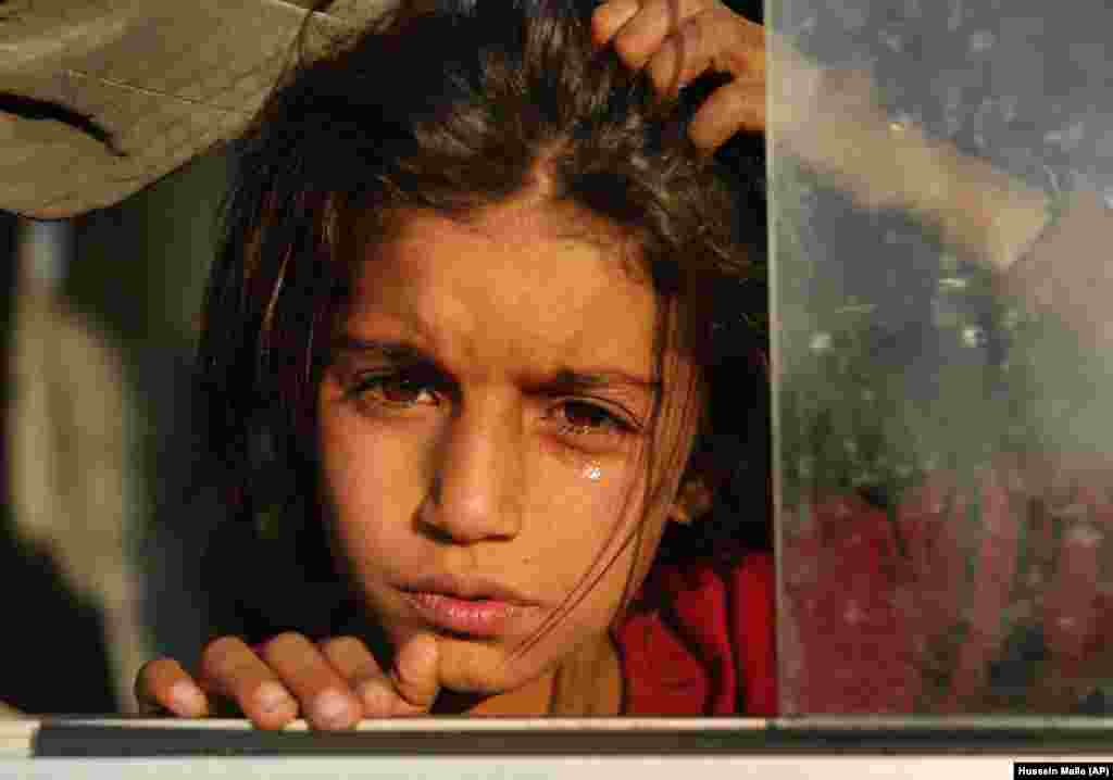 A girl newly displaced by a Turkish military operation in northeastern Syria weeps as she sits in a bus upon her arrival at the Bardarash camp, north of Mosul, Iraq. (AP/Hussein Malla)