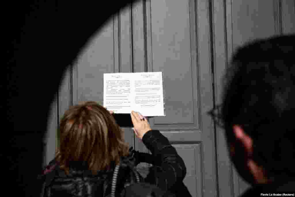 Женщина читает объявление на двери оперного театра «Ла Скала», закрытого из-за вспышки коронавируса в регионе