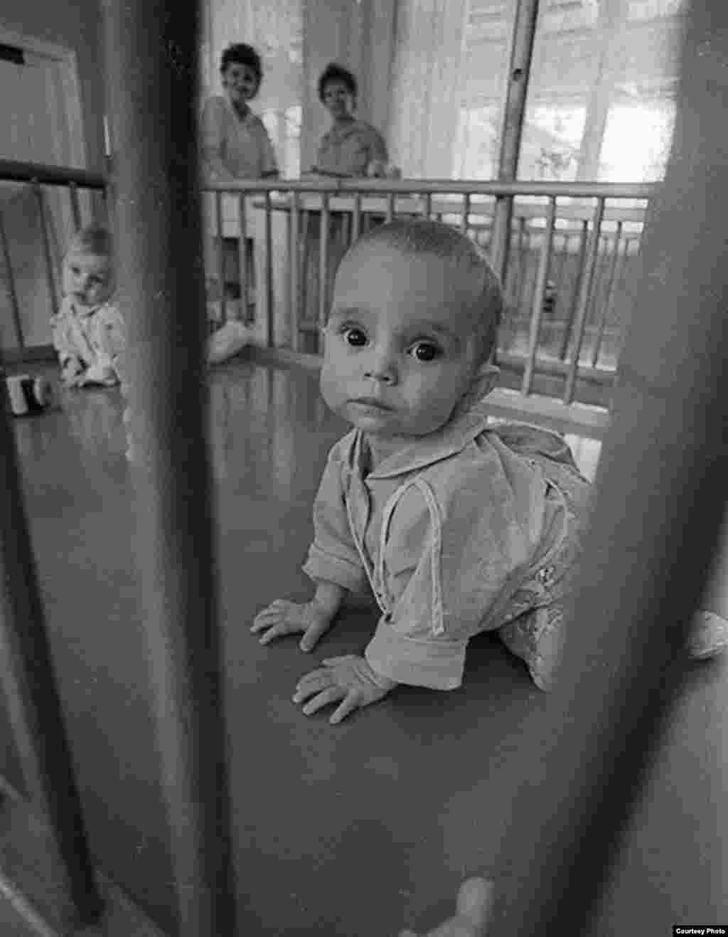 St. Petersburg-based photographer Aleksandr Belenky has spent years documenting the lives of children inside Russian orphanages. Here, a baby boy plays inside a crib in an orphanage in central St. Petersburg in 1991.