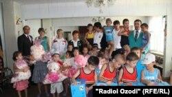 Tajikistan,Dushanbe city, a tajik participant in London Oympic -2012 presenting a gift to a scholol children,18July,201