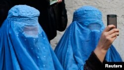 A burqa-clad woman takes photos with her mobile phone. (file photo)