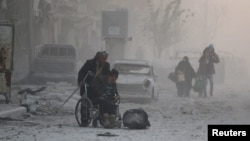 A man in a wheelchair flees with others into the remaining rebel-held areas of Aleppo on December 9.