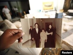 Jedna od fotografija pronađenih u Gadafijevoj rezidenciji prikazuej Gadafija sa suprugom Safijom i sinom Saifom Al Islamom, 2011.