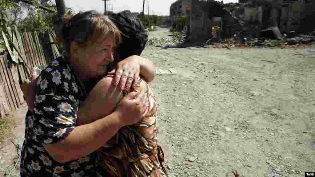 Женщины обнимаются среди руин Цхинвали. Город подвергся немалым разрушениям во время боевых действий