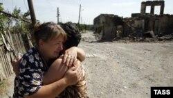 Осетинские женщины обнимают друг друга на фоне руин разрушенного города Цхинвали, столицы непризнанной республики Южная Осетия. Август 2008 года.