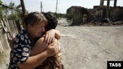 Грузия-Ресей соғысынан қираған Оңтүстік Осетияның қираған қаласы Цхинвалиде екі әйел құшақтасып тұр. Тамыз, 2008 жыл.