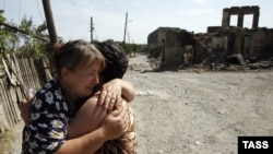 Two women hug each other amid ruins in the South Ossetian capital of Tskhinvali, which was devastated by the brief Georgian-Russian conflict in 2008.