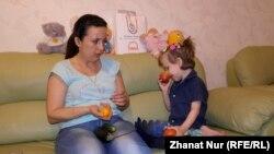 Елена Хижняк көзі көрмейтін қызы Елизаветаны ойнатып отыр. Астана, 14 мамыр 2014 жыл