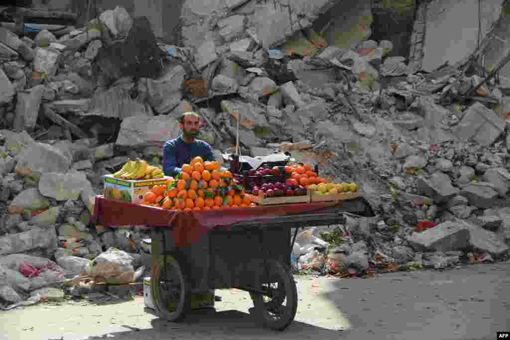 A fruit vendor waits for customers next to a damaged building in the Shaar neighborhood of the northern Syrian city of Aleppo. (AFP/Mohammed al-Khatieb)