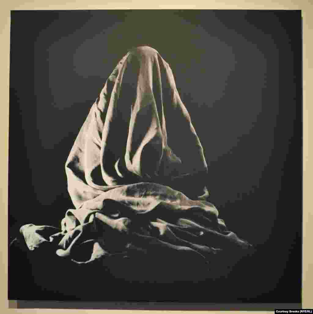 A hunched-over figure is shrouded beneath a blanket.