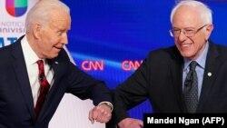 Джо Байдэн (зьлева) і Бэрні Сандэрс вітаюцца перад дэбатамі ў студыі CNN у Вашынгтоне, 15 сакавіка 2020