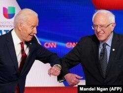 Gjatë një debati, Joe Biden dhe Bernie Sanders u përshëndetën me bërryla, duke shmangur shtrëngimin e duarve për shkak të koronavirusit.