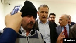Turkey -- Zaman editor-in-chief Ekrem Dumanli (C) is escorted by plainclothes police officers as he leaves his office at the headquarters of Zaman daily newspaper in Istanbul, December 14, 2014