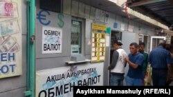 Люди у пункта обмена валют на рынке в Алматы. 14 августа 2015 года.