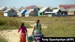 Members of the Roma community walk back home in the village of Pidvynogradiv near the Ukrainian city of Vynogradiv