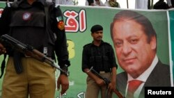Police stand guard near a portrait of Nawaz Sharif during a campaign rally in Peshawar.