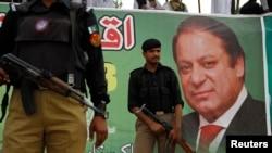 Полицейские у предвыборного плаката Наваза Шарифа в Пешаваре