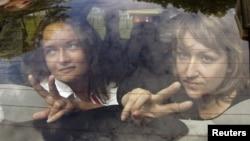Ірина Козлік (л) і Юлія Дарашкевич (п) у машині міліції біля суду в Мінську 9 серпня 2012 року