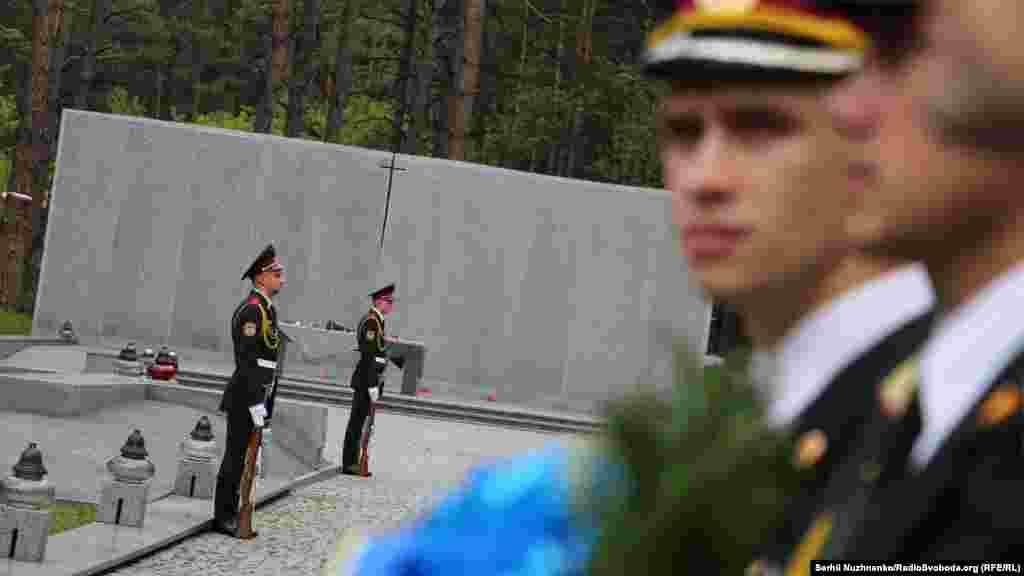 Почетный караул охраняет польский мемориал и стену с сотнями высеченных польских имен