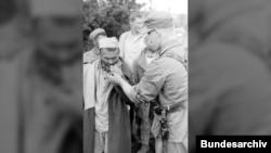 Немецкий солдат дает прикурить советскому пленному, июнь 1943 года