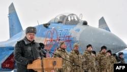 Ukrainian servicemen listen on as Ukrainian President Petro Poroshenko gives a speech as he announces the handover of new military equipment to the Ukrainian forces in early January.