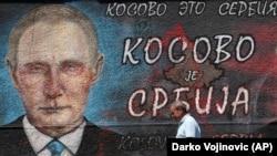 """Прохожий в Белграде на фоне графити с надписью: """"Косово – это Сербия"""", август 2019"""
