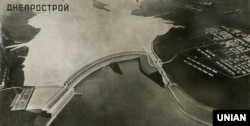 Репродукція архівного фото, на якому зображено утверджений проект ДніпроГЕС (Дніпровська гідроелектростанція) під час будівництва, влітку 1931 року