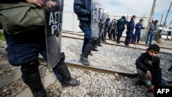 პოლიცია და მიგრანტი ბავშვი საბერძნეთ-მაკედონიის საზღვარზე