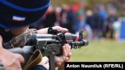 Ребенок стреляет из тренировочного автомата АК-47 в тире во время празднования российского «Дня народного единства» в Симферополе, 4 ноября 2017 года