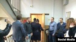 Александр Белов (Поткин) соты өтіп жатқан залдың есігінде тұрған адамдар.
